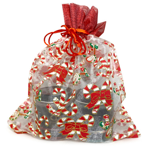 An image of two jars of holiday Just Dessert flavors inside a festive organza bag patterned with ribbons and candy canes with a red ribbon tie.
