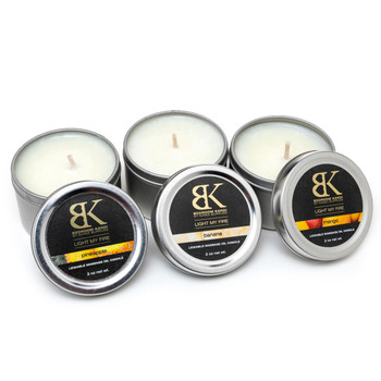 An image of three small flavored massage oil candle tins in a row with their lids propped up in front of them, displaying the flavors.