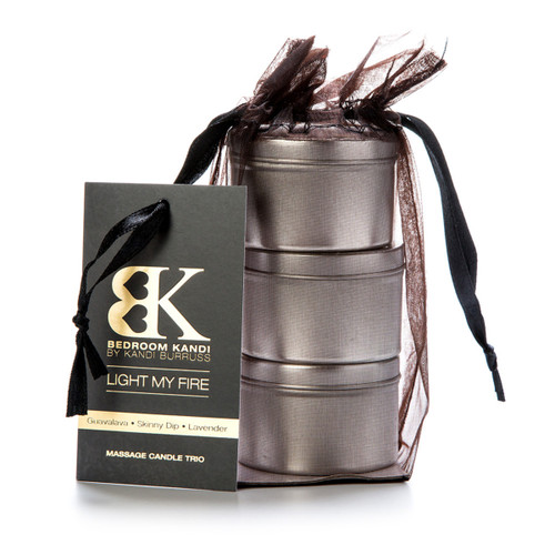 "An image of three small massage oil candle tins stacked on top of each other in a black organza bag. A tag attached to the bag reads ""Light My Fire"" and lists the fragrances."