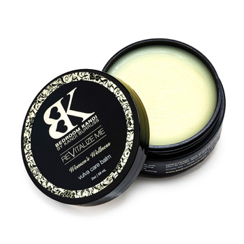 An open jar of the ReVitalize Me vulva care balm, the lid propped against the container, revealing the pale yellow surface of the balm inside.