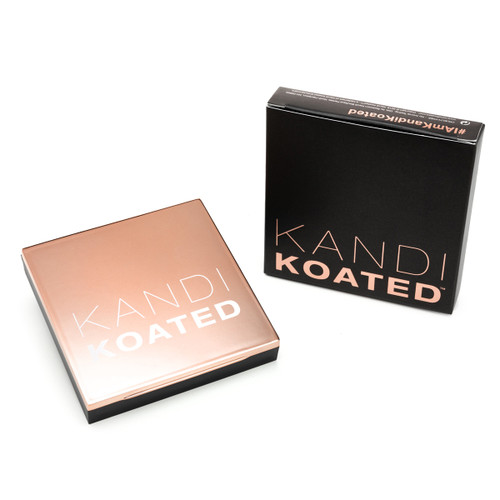 An image of a square compact with a rose gold lid with the frosted Kandi Koated logo. Beside it is its packaging, a black box with rose gold lettering. Both sit on a white background.