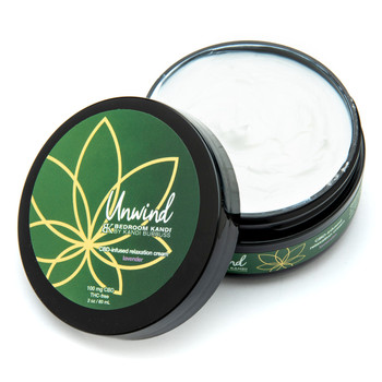 An open two ounce black round jar of Unwind CBD-infused relaxation cream. The label is green and gold over a black jar on a white background. The thick white cream is visible inside the jar.