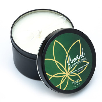 An image of the Unwind Massage Oil Candle tin. The lid is off and propped against the side of the tin, revealing the pale wax, wick, and a small plastic spoon for removing the melted oil.